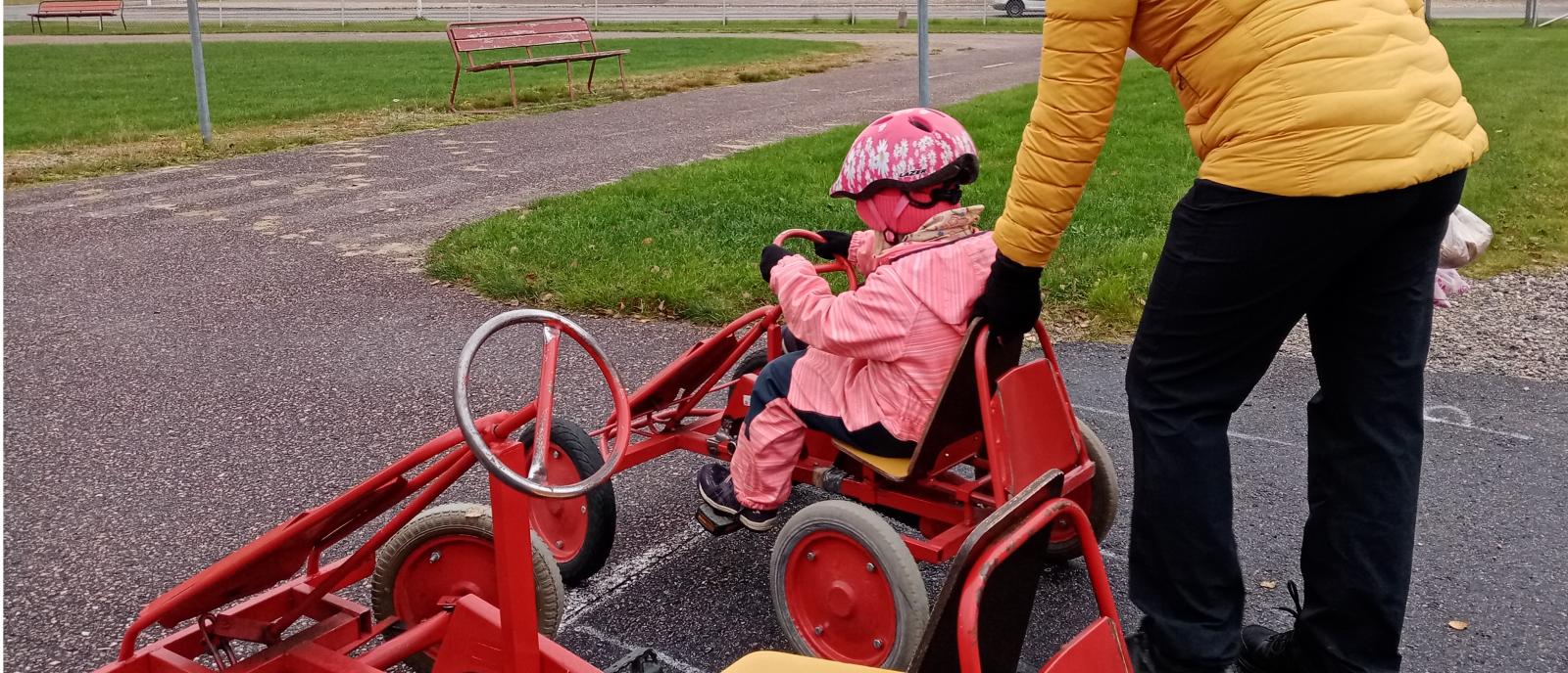 Lapsi polkuautossa ja vanhempi seisoo takana