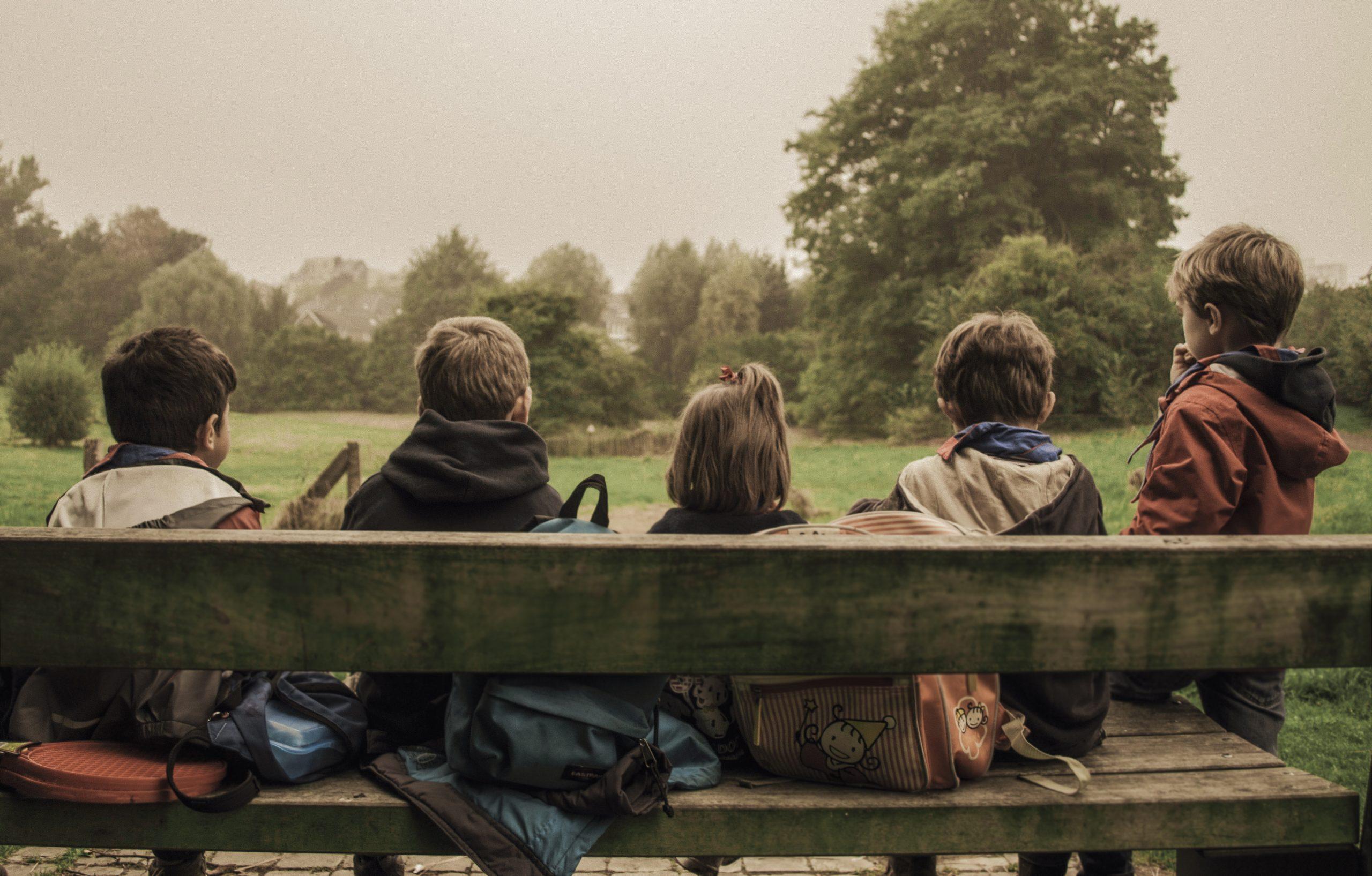 Pienet koululaiset istuvat ulkona