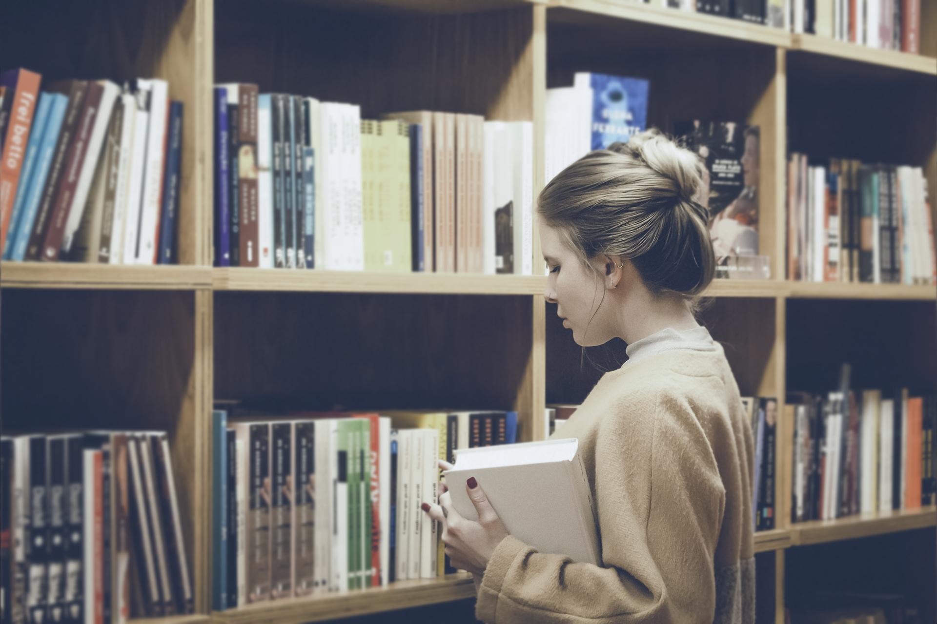 Tyttö selaa kirjaston kirjoja