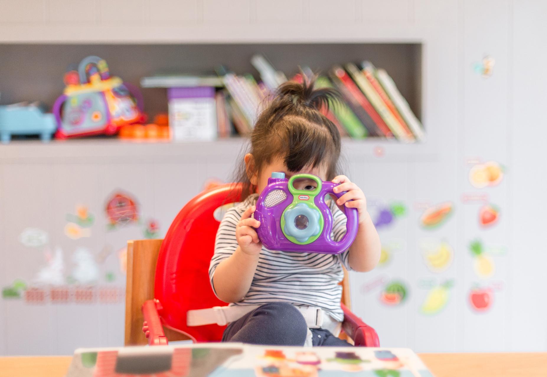 Pikku tyttö katsoo lelukameran linssin läpi