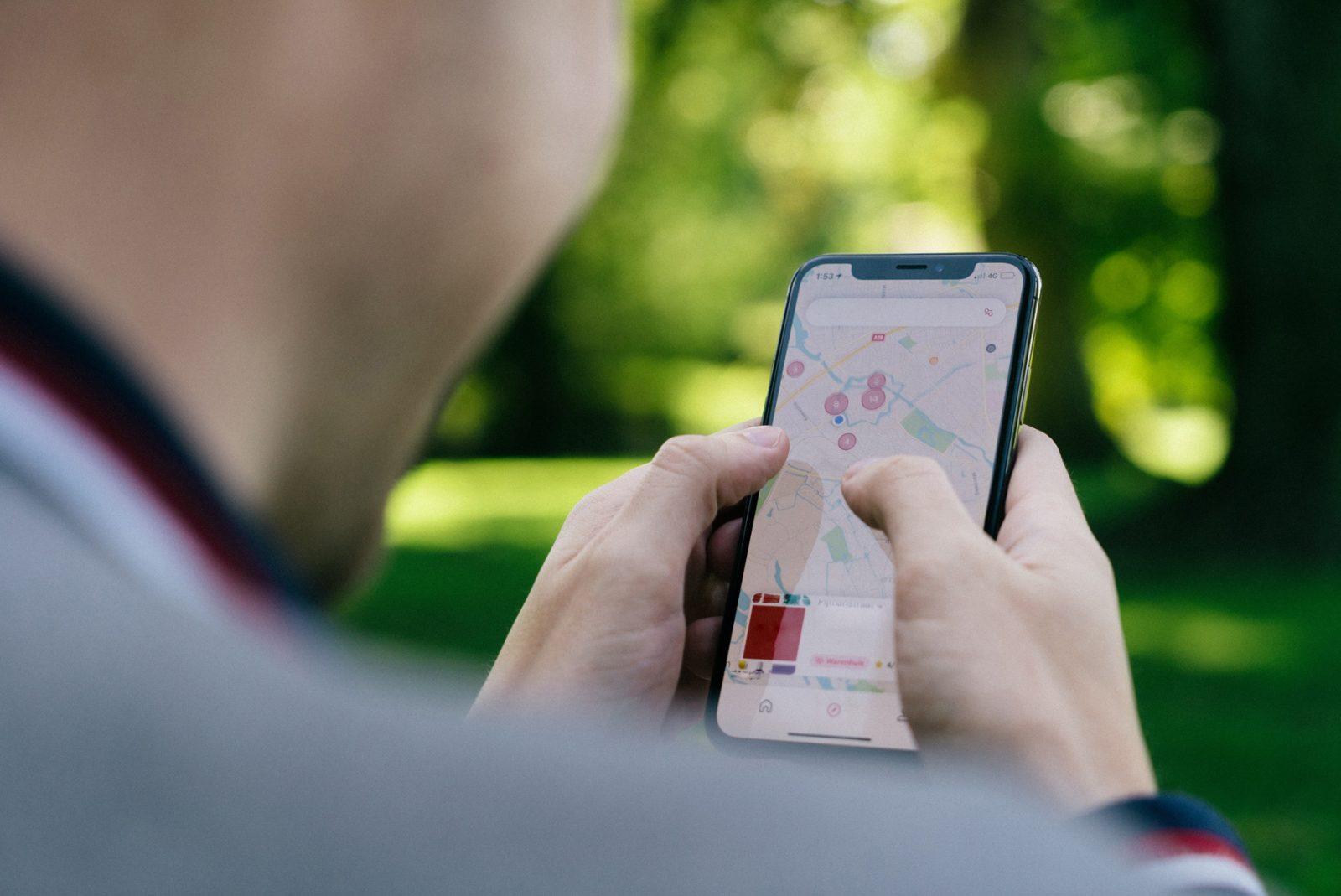 Mies katsoo puhelimesta karttaa