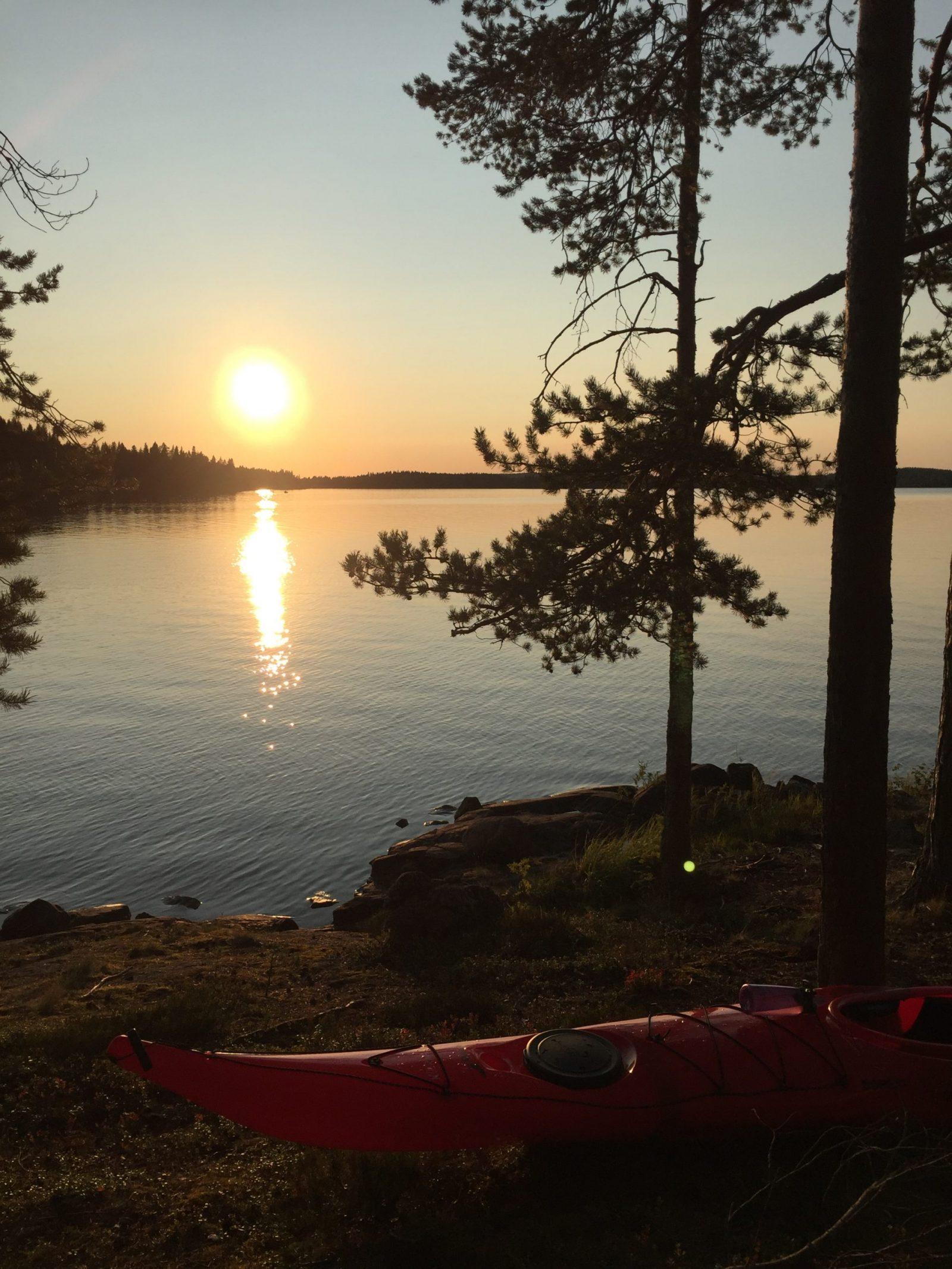 Rannalta otettu kuva kajakista ja auringonlaskusta Rehjansaaressa.