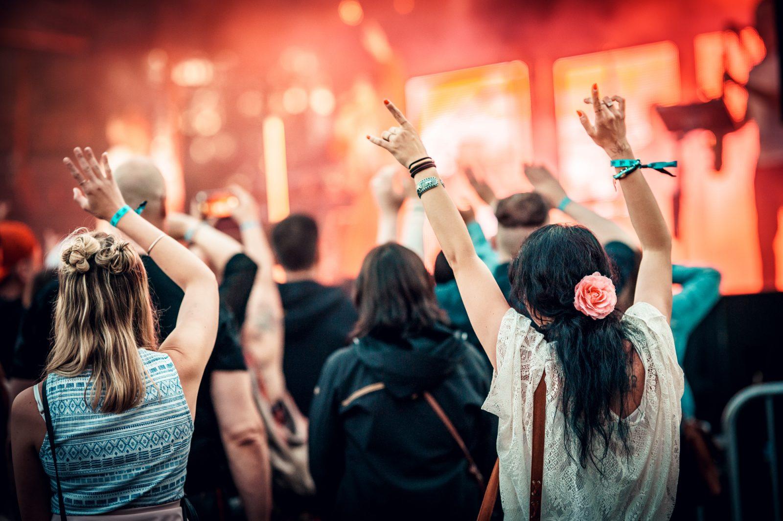 Ihmisiä festareilla kädet ilmassa