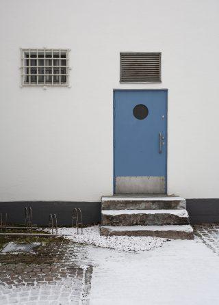 Kuvassa Kajaanin taidemuseon sisäpihan ovi pyöreine ikkunoineen sekä putkan kalteri-ikkuna.