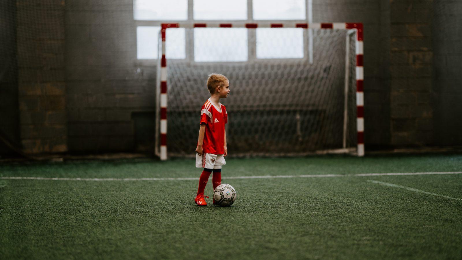 Pikkupoika pelaamassa jalkapalloa