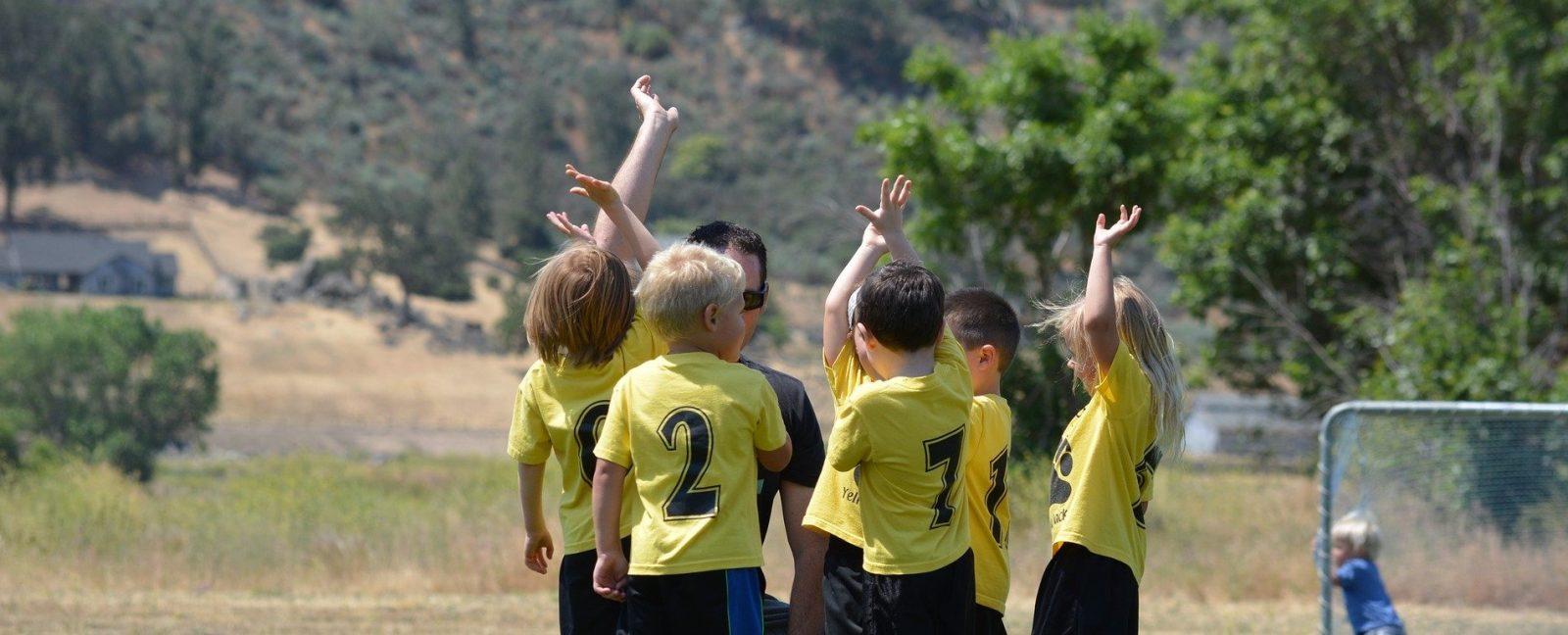 Lasten jalkapallojoukkue juhlii valmentajan ympärillä
