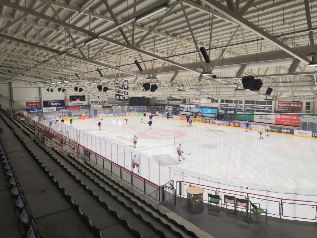 Jääkiekon pelaajia kisajäähallin kaukalossa. Kuva otettu katsomosta.