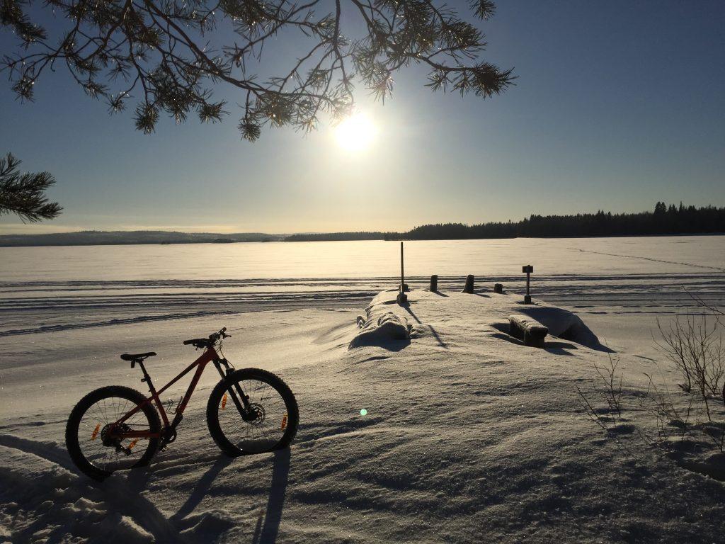 Rehjansaarelta talvella otettu kuva kohti matalalla paistavaa aurinkoa. Maastopyörä on kinoksessa pystyssä.