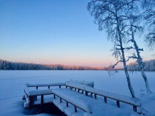 Ruuhijärven laituri talvella. Taustalla aurinko valaisee kaukaisia puiden latvoja.