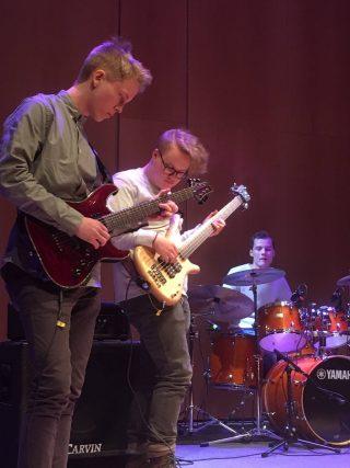 Kaksi kitaristia ja rumpali soittavat bändissä