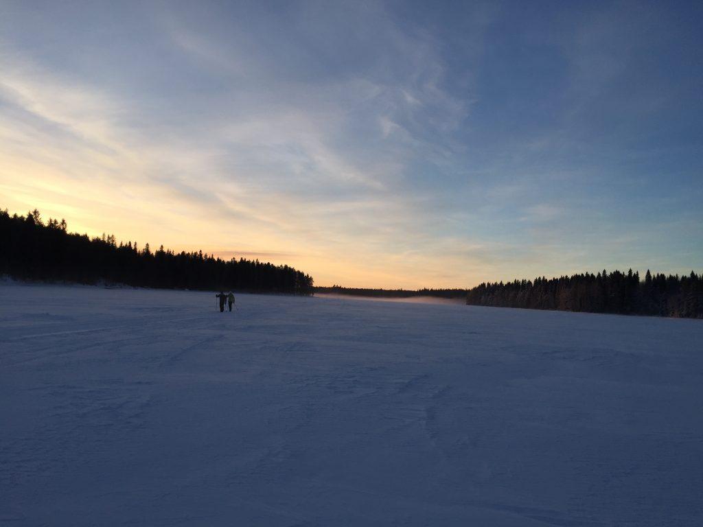 Kaksi hiihtäjää Rehjansalmella auringonlaskussa