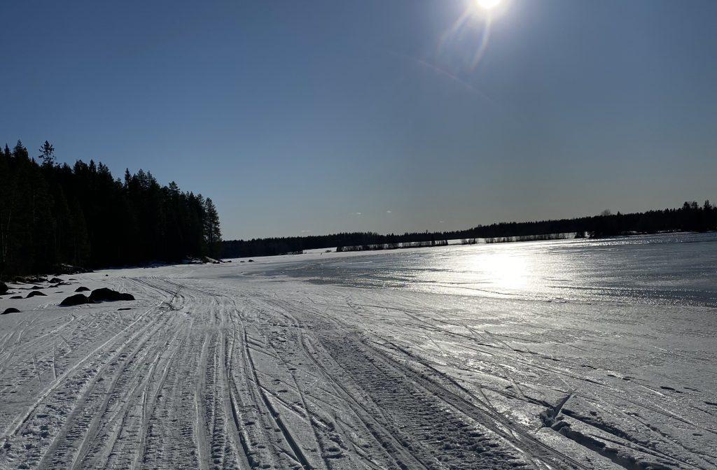 Hiihtäjän kuva järviladulta. Pilvetön aurinkoinen taivas heijastuu järven pinnasta.