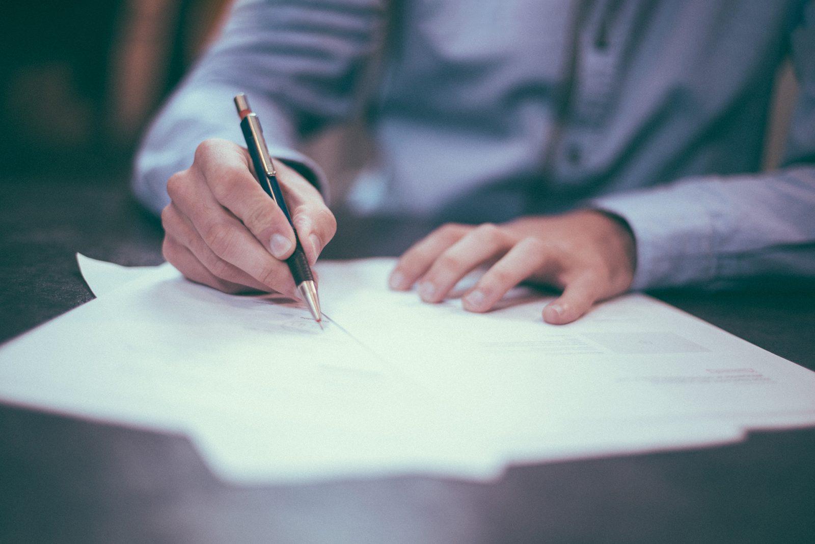 Henkilö kirjoittamassa papereita