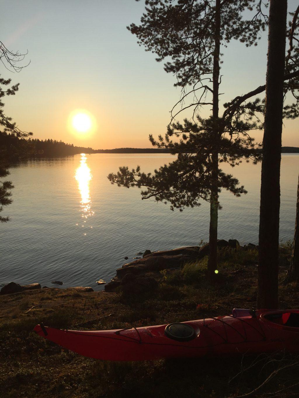 Kuva kanootista Rehjansaaren rannalla. Taustalla auringonlasku