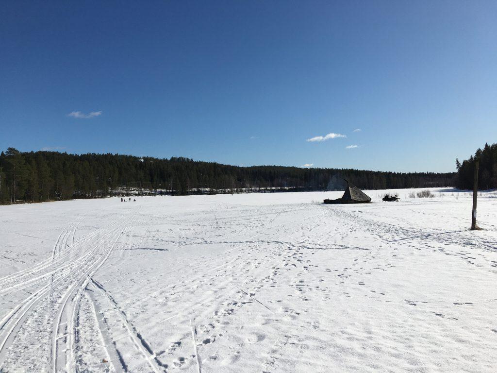 Kuvassa Vimpelinlammen laavu talvella. Lammen jäällä hiihtäjiä.