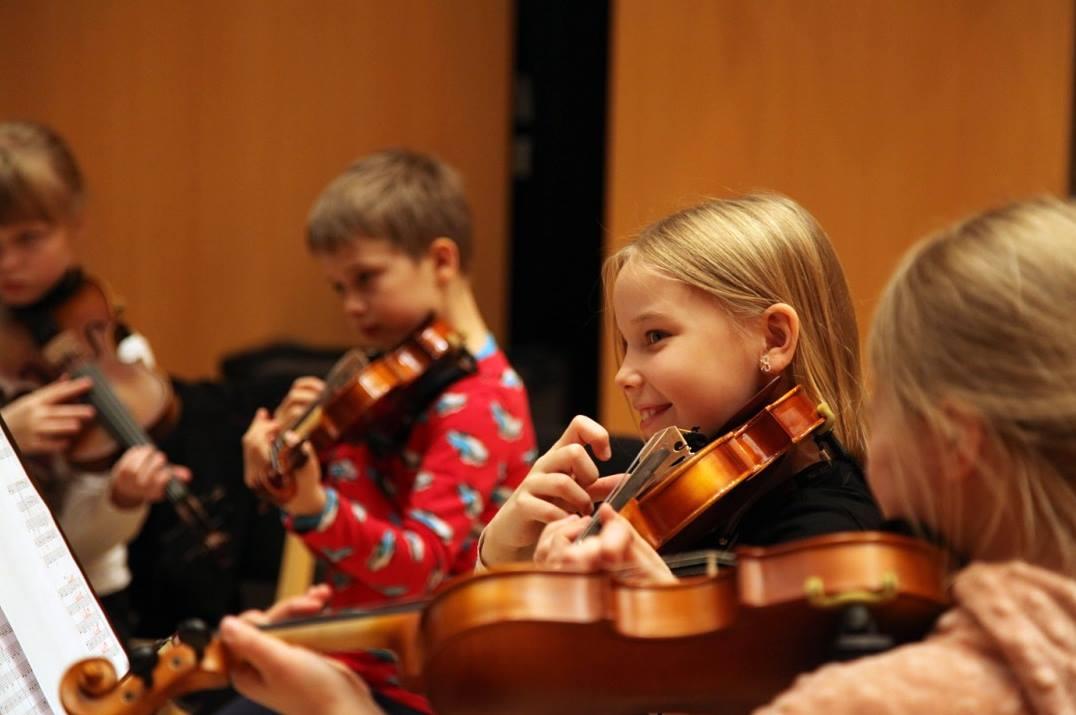 Lapset soittavat viulua orkesterissa