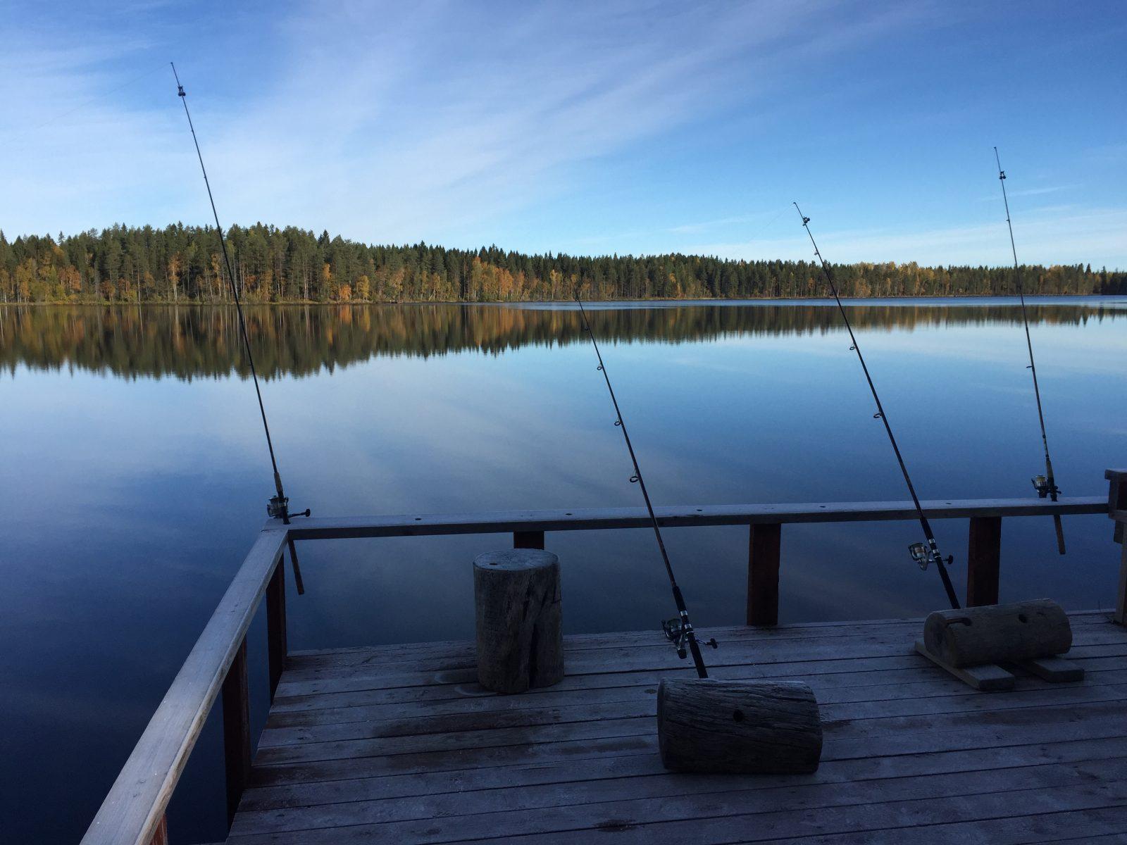 Ruuhijärven laiturilla virveleitä pystyssä, taustalla tyyni järvi.