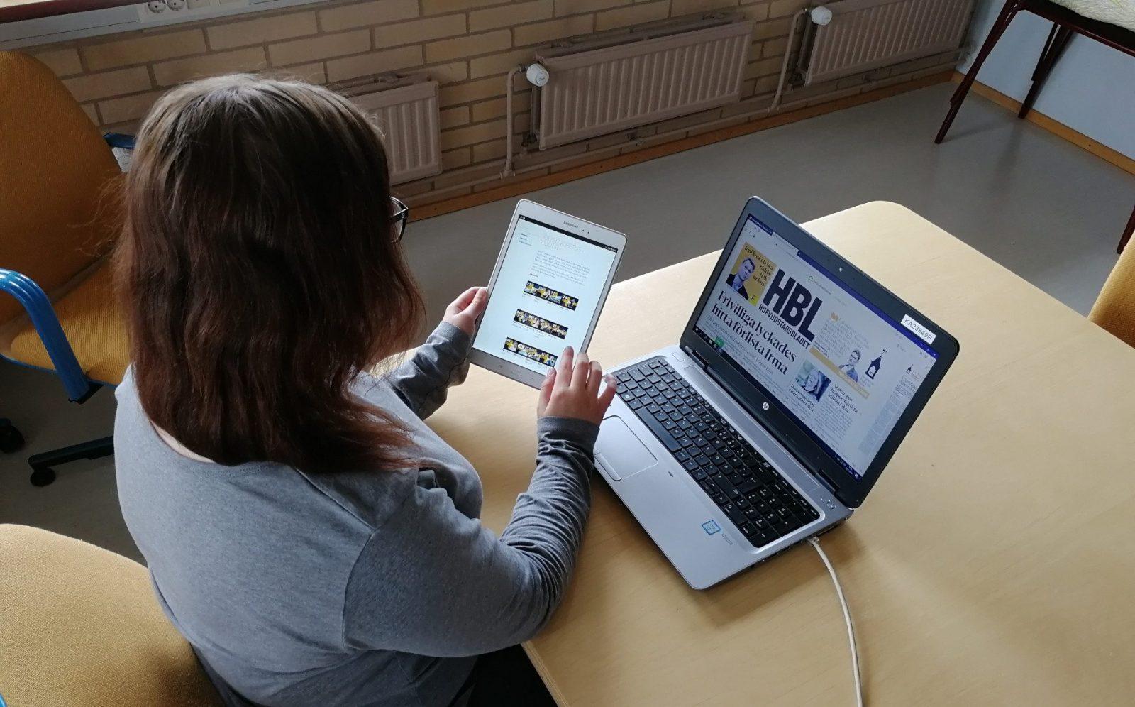 Nainen selaa eKirjaston palveluita tabletilla ja tietokoneella.