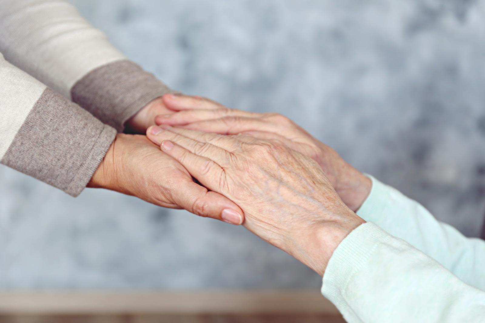 Vanhemman henkilön kädet ovat vasten nuoremman henkilön käsiä