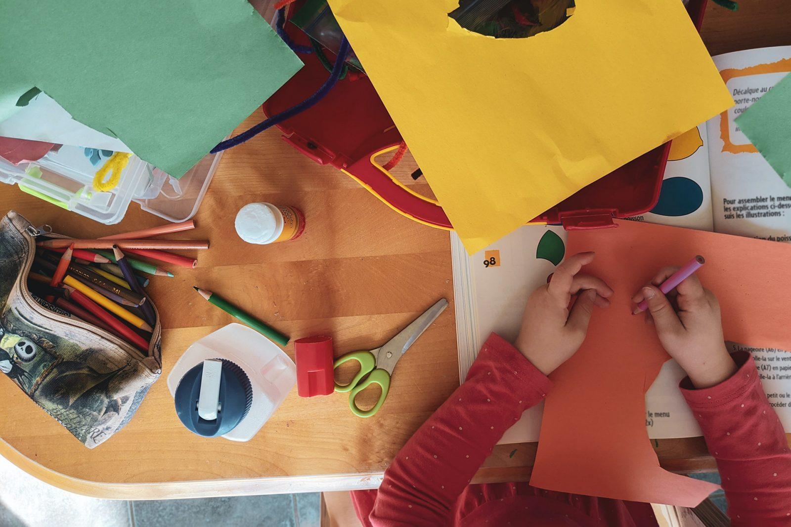 Askarteluvälineitä ja lapsi askartelemassa