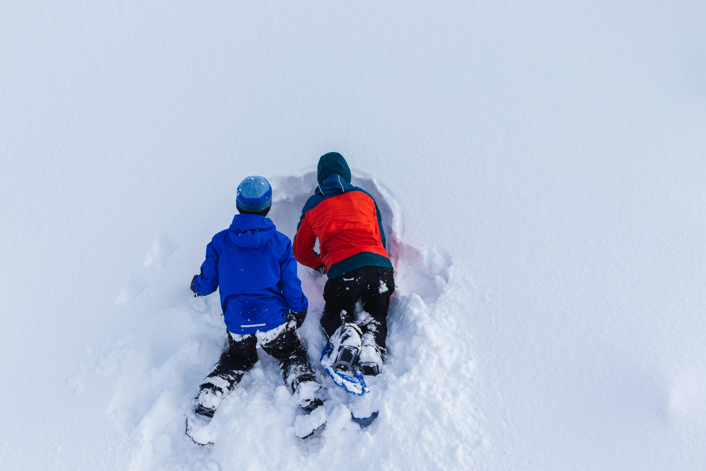 Kaksi lasta makaa mahallaan hangessa lunta kaivamassa.