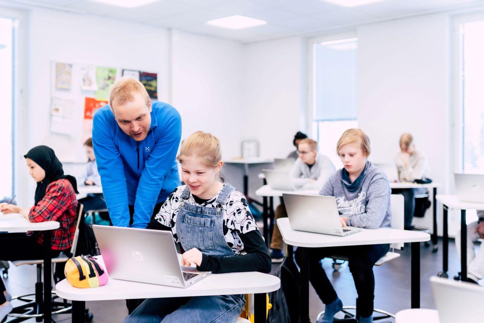 Opettaja ja oppilas käyttävät yhdessä tietoteknisiä välineitä