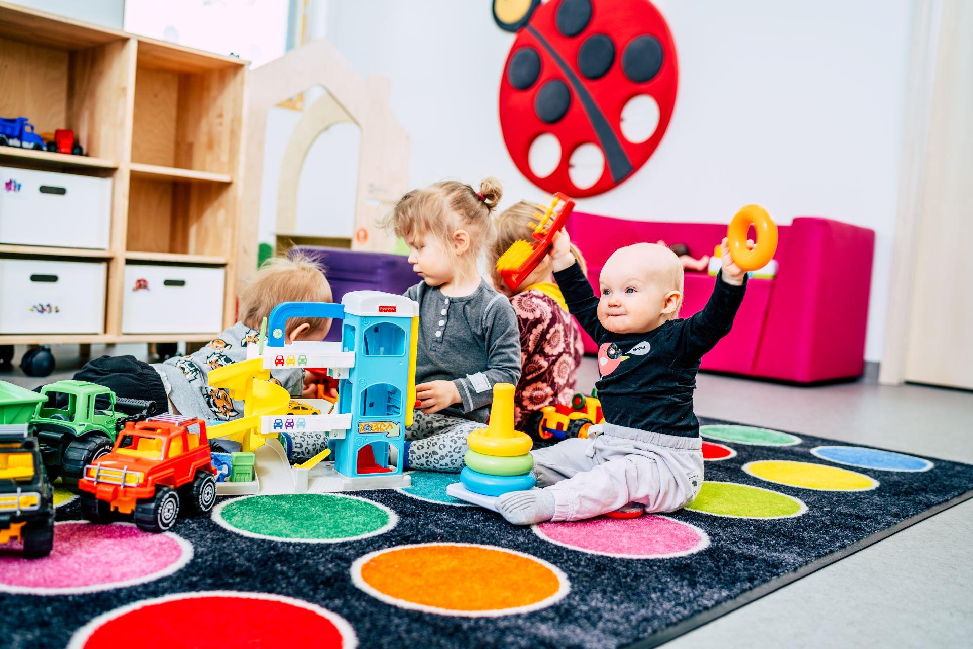 Lapset leikkimässä leikkimaton päällä