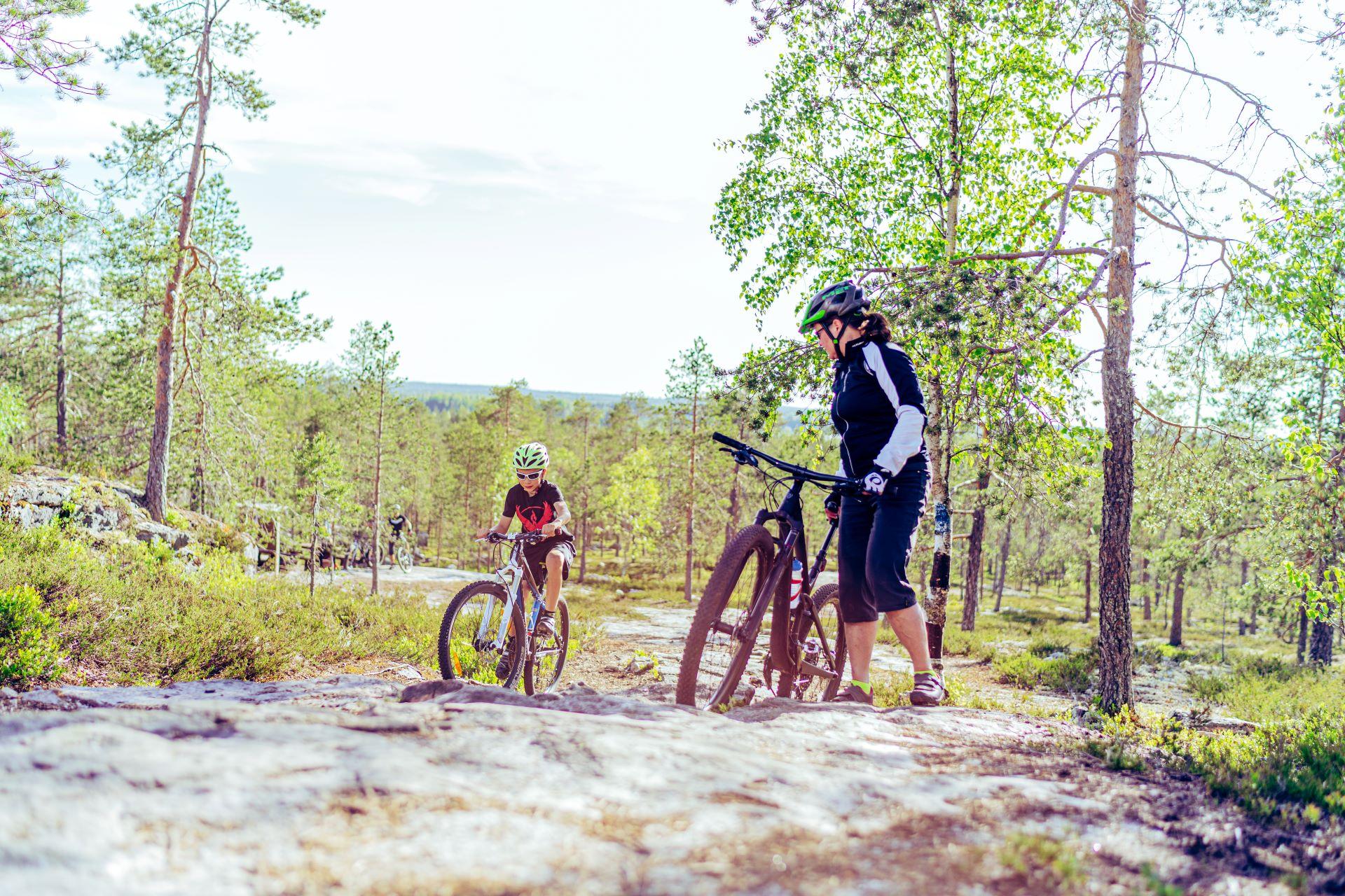 Metsämaisema, jossa nainen on pysähtynyt pyörän viereen katsomaan kun poika ajaa kallioista polkua pitkin ylöspäin.
