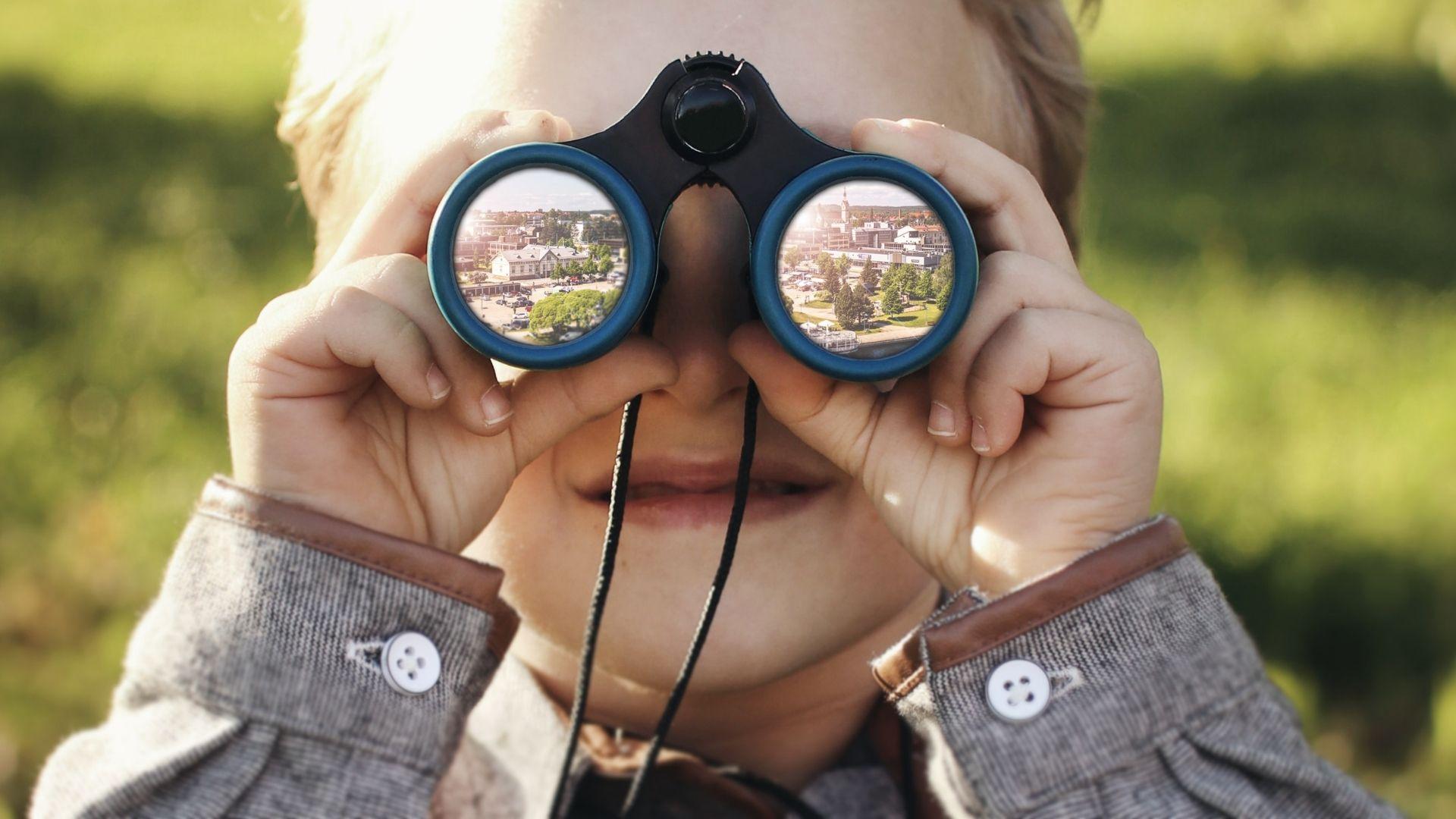 Lapsi tähystää kiikareilla kaupunkiin