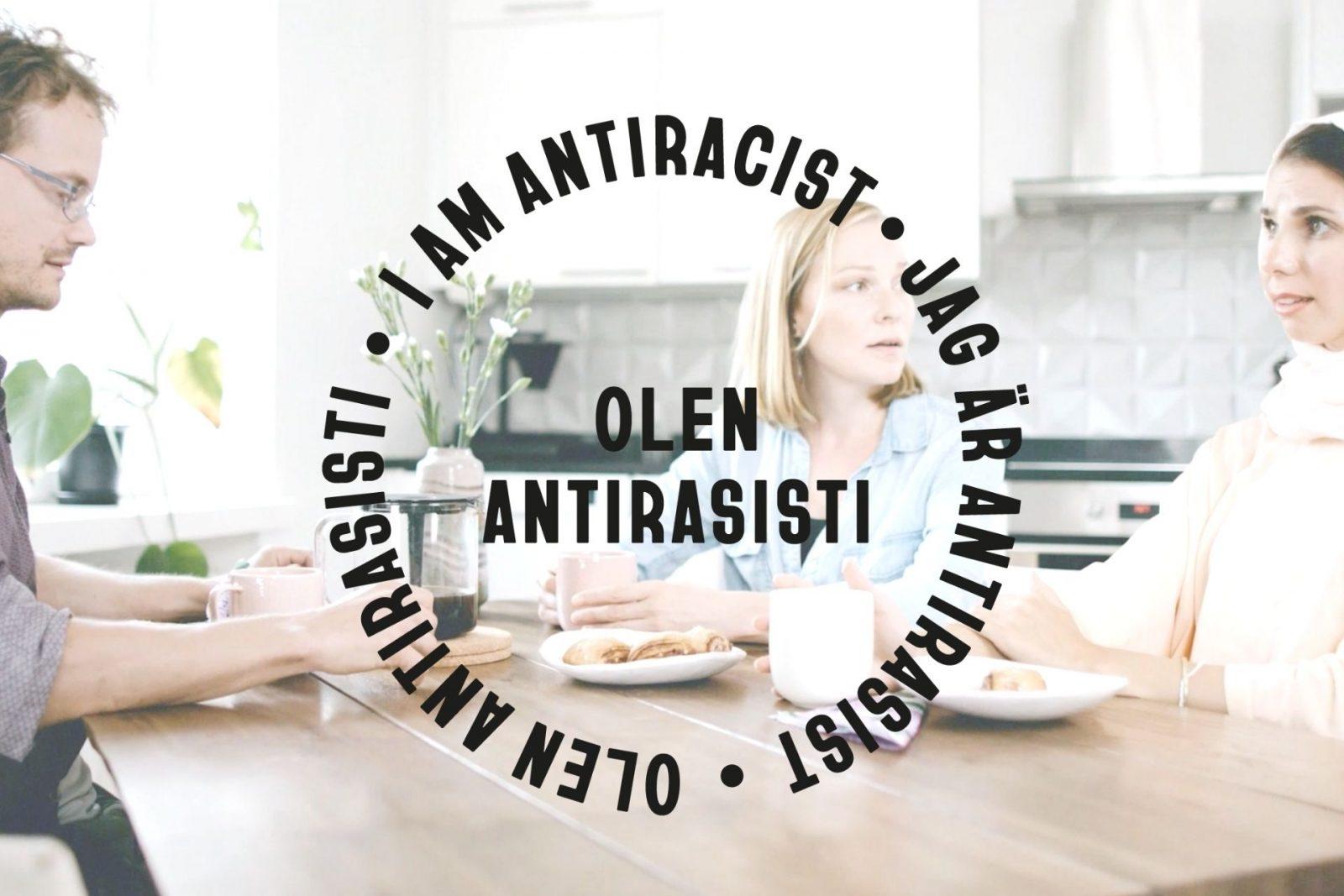 Kaksi naista ja mies istuvat kahvipöydässä. Kuvan päällä lukee olen antirasisti.